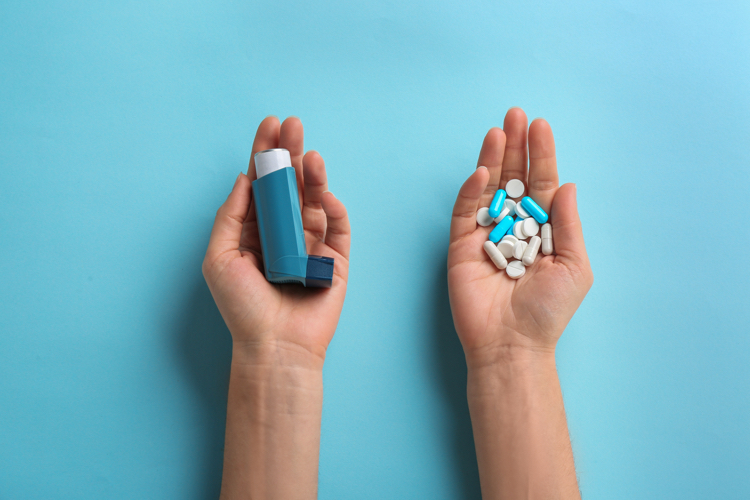 Two hands with an inhaler in one and pills in the other for patient market research