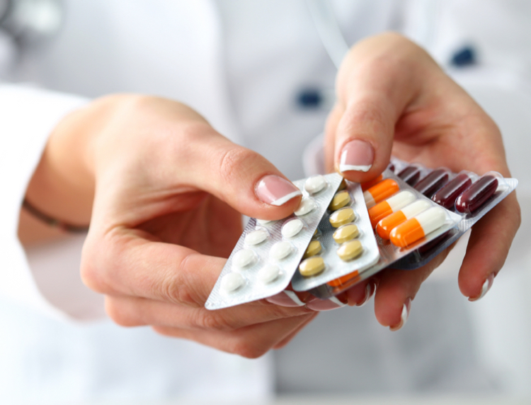 Person in a white coat holding out an array of pills - Patient market research