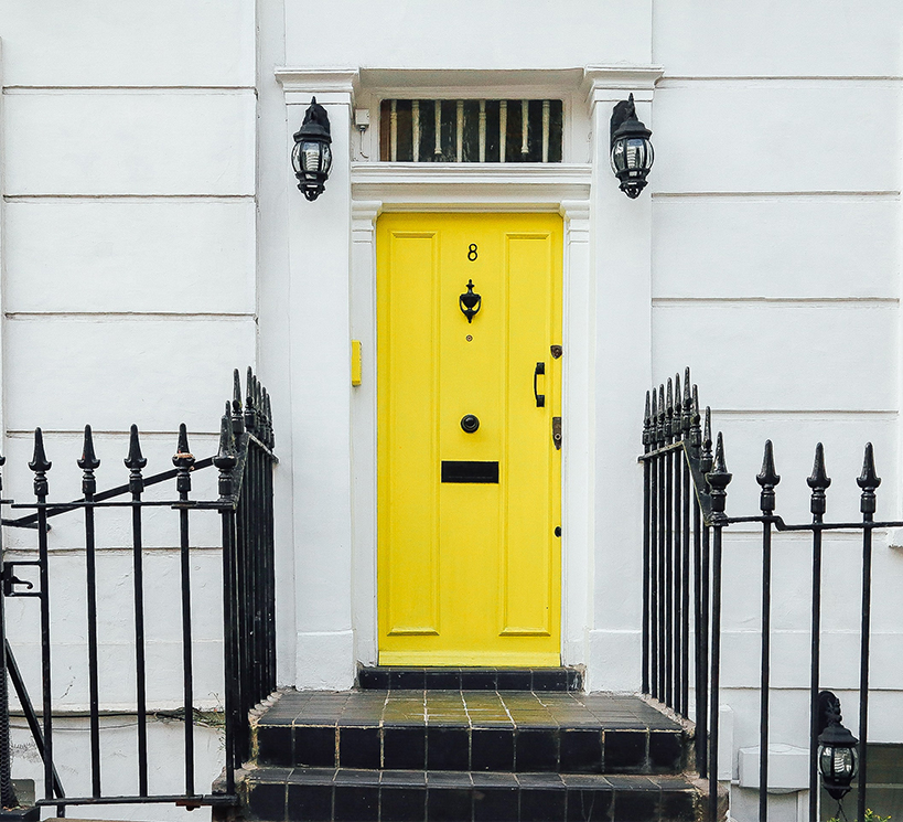 A picture of a yellow front door with the number 8 on it